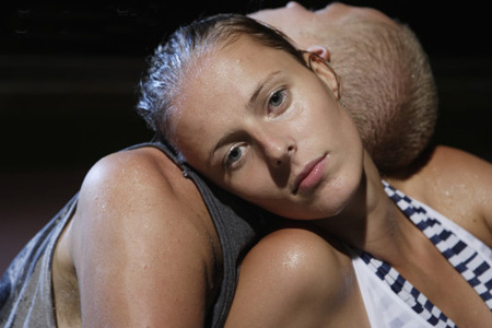 Young sweaty couple leaning on each other, portrait of woman